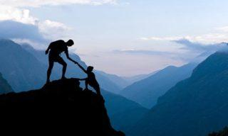 Man helping another person climb to the top of the mountain