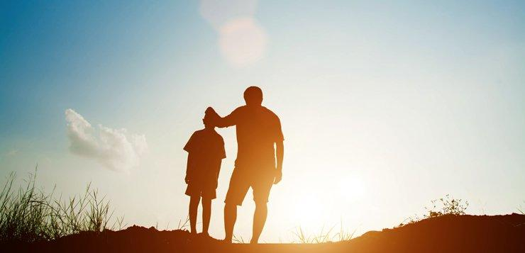Silhouette of father and set standing while looking at the sky and sunrise